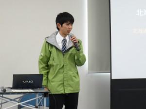 写真2.副賞として授与されたモンベル社製レインウェア「フィールド レインジャケット」を羽織って講演する河村さん.
